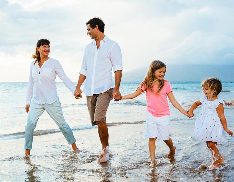 Mom, Dad and two girls walking on the beach